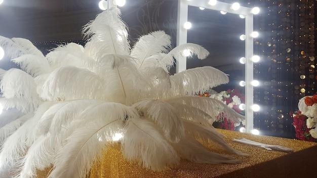 Plumas de avestruz decorativas sobre una mesa dorada junto a un espejo de maquillaje.