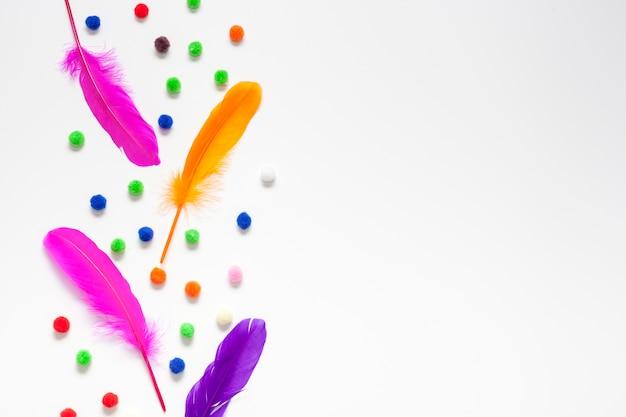 Plumas de colores y bolas de algodón copia espacio