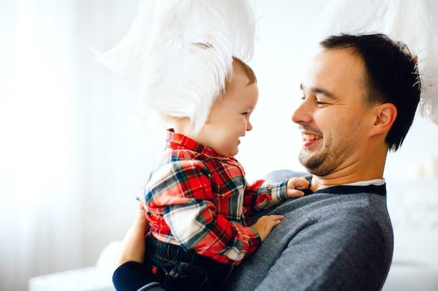 Las plumas cuelgan sobre papá sosteniendo a su pequeña hija