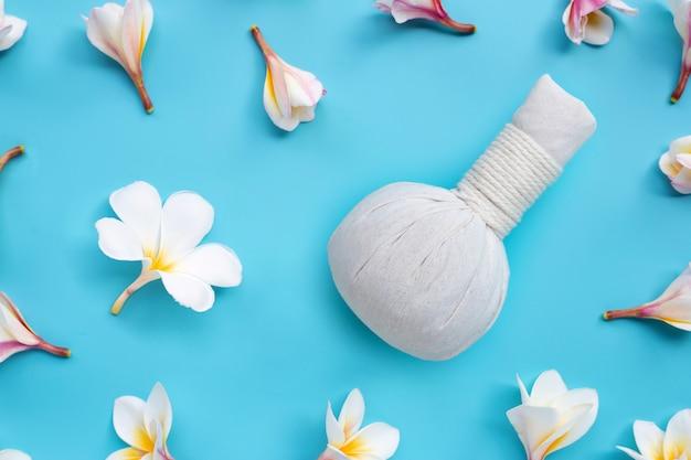 Plumeria o flor de frangipani con bola de compresas herbales para masaje tailandés y tratamiento de spa