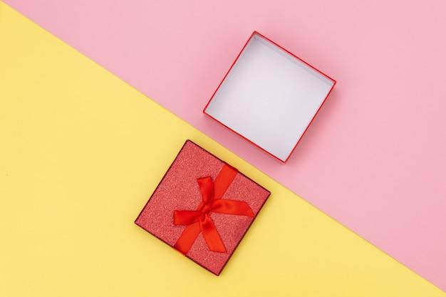 Poca caja de regalo abierta sobre fondos rosados y amarillos.
