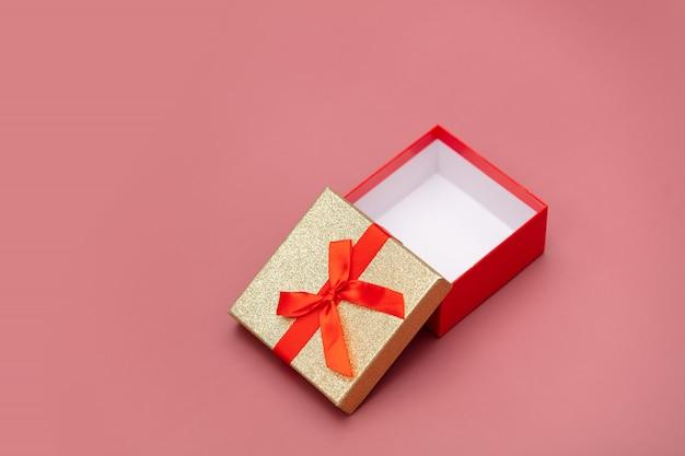 Poca caja de regalo sobre fondo rosa.