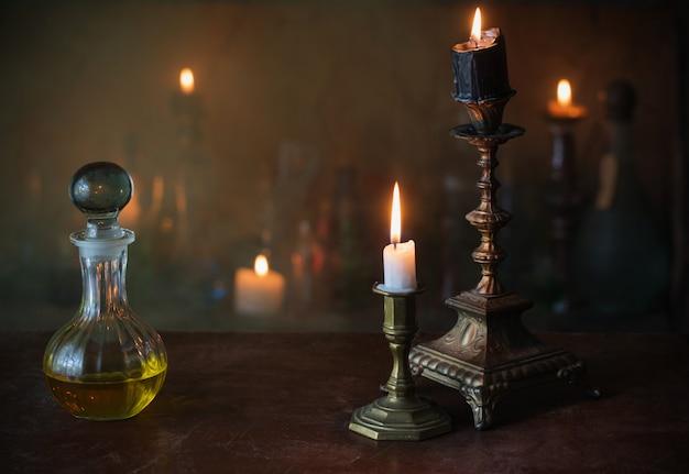 Poción mágica, libros antiguos y velas en la oscuridad.