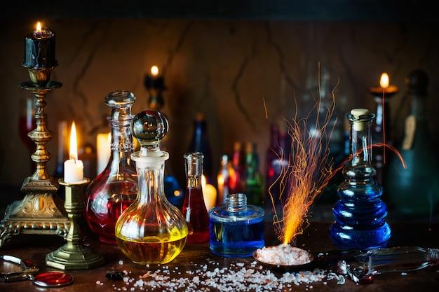 Poción mágica, libros antiguos y velas sobre fondo oscuro