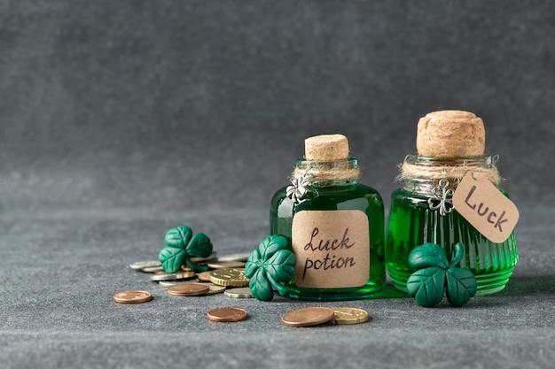 Poción de la suerte en botellas, hojas de trébol hechas a mano y dinero.