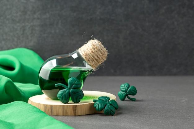 Poción de la suerte en frasco y hojas de trébol hechas a mano.