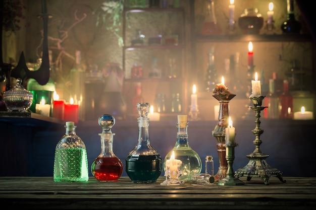Pociones mágicas en botellas sobre fondo de madera