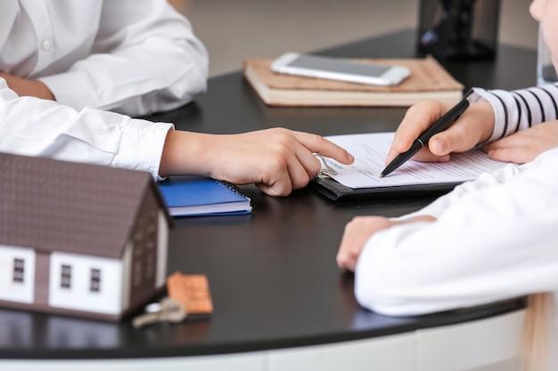Poco agente inmobiliario que trabaja con clientes en la oficina