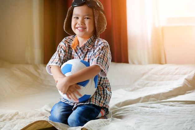 Poco asiático niño jugando con la pelota, viajes y concepto de aventura