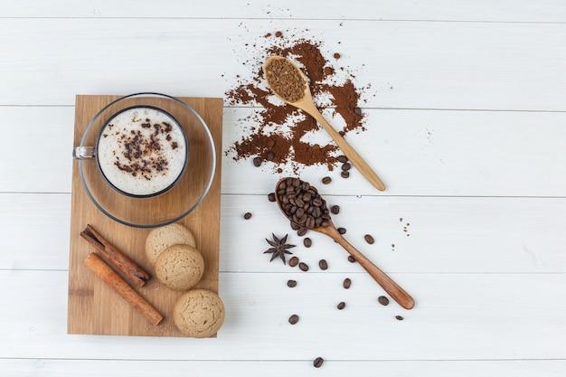 Un poco de café con café molido, granos de café, palitos de canela, galletas en una taza sobre fondo de madera y tabla de cortar, endecha plana.