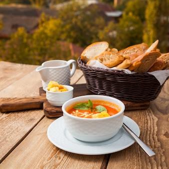 Un poco de comida deliciosa sopa con pan en un tazón con bosque en el fondo, vista de ángulo alto.