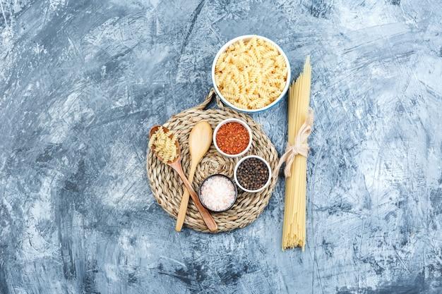 Un poco de pasta fusilli con espaguetis, cucharas de madera, especias en un recipiente sobre fondo gris de yeso y mantel de mimbre, vista superior.