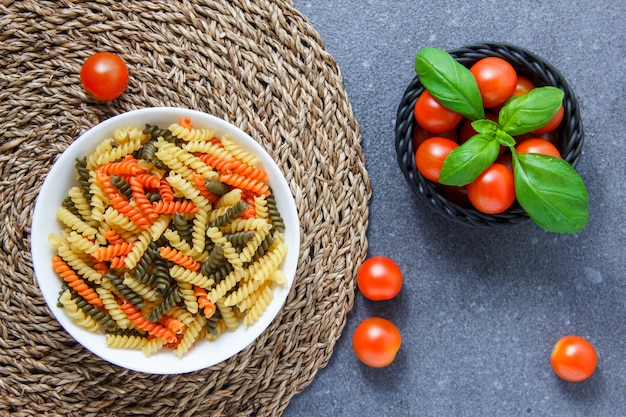 Un poco de pasta de macarrones de colores con tomates y hojas en un tazón sobre trébede y superficie gris, vista desde arriba.