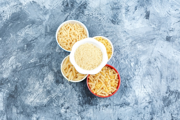 Un poco de pasta variada en tazones sobre fondo de yeso gris, vista superior.