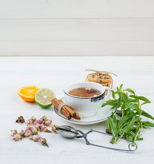 Un poco de té de hierbas con colador de té, hierbas, frutas cítricas y galletas.