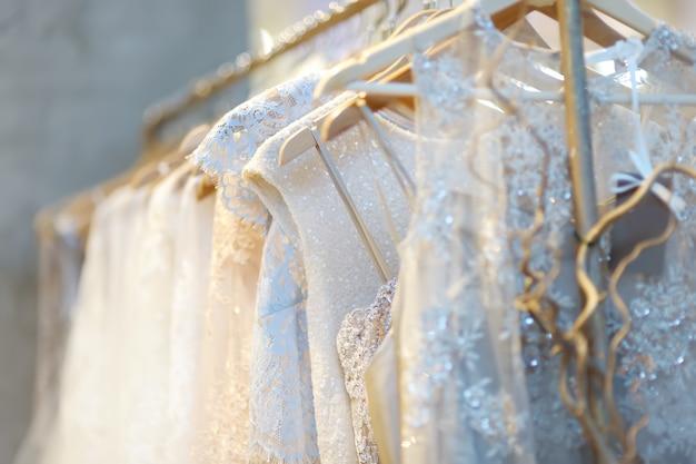 Pocos hermosos vestidos de novia en una percha.