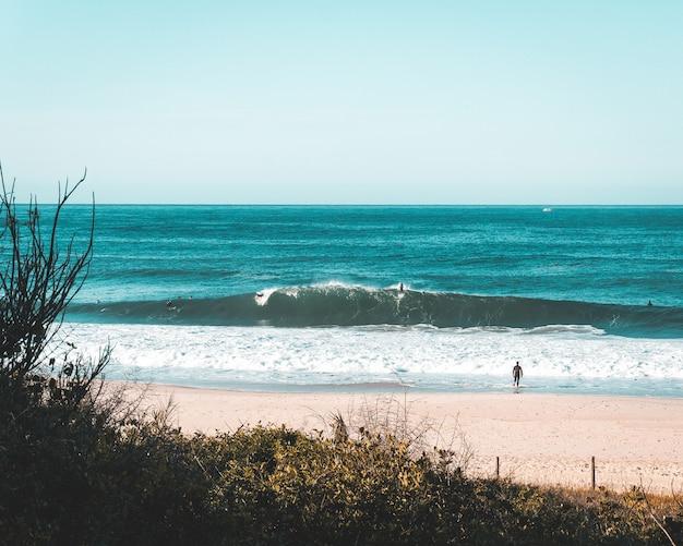 Pocos surfistas en la costa del mar.