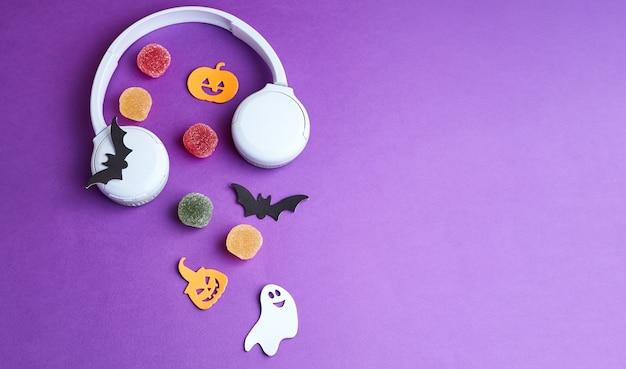 Podcast de halloween. decoraciones de halloween, calabazas, murciélagos, dulces, fantasmas, sobre fondo morado. tarjeta de felicitación de fiesta de halloween. copie el espacio. endecha plana, vista superior, arriba.