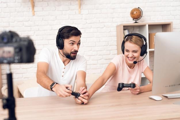 Podcasters de hombre y mujer juegan videojuegos para podcast.