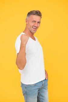 Poder de los hombres. hombre feliz arreglar fondo amarillo del brazo. soltero muestra la potencia muscular. estilo casual y tendencias de moda. potente y seguro. la confianza es poder.