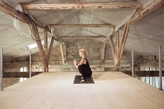 Poder. una joven atlética ejercita yoga en un edificio de construcción abandonado. equilibrio de salud mental y física. concepto de estilo de vida saludable, deporte, actividad, pérdida de peso, concentración.