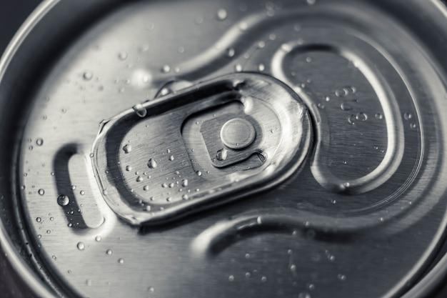 Poder de metal cerrada de cola sobre fondo negro. vista superior. se puede beber con gotas de agua. botella de cerveza de acero brillante.