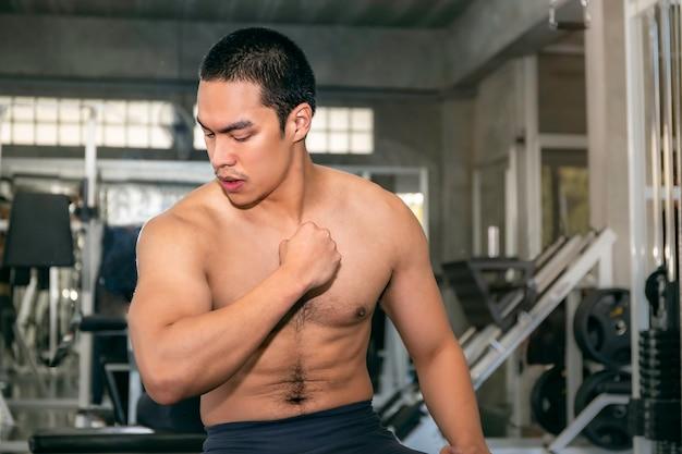 Poder musculoso guapo hombre asiático fuerte y saludable sonriendo en el gimnasio después del entrenamiento.