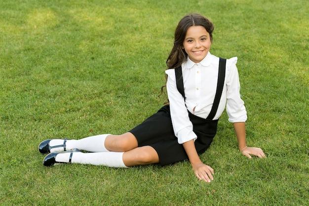 Poder en nuestra juventud. alumno sonriente se sienta en la hierba. divertirse. niño feliz relajándose al aire libre. colegiala alegre. minuto para relajarse. colegiala relajante. concepto de infancia feliz. día internacional de la infancia.