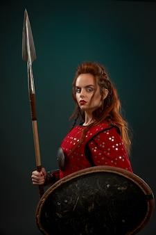 Poderosa luchadora con armadura que mantiene la lanza y el escudo