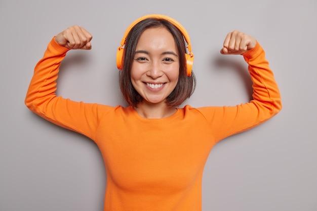 Poderosa mujer asiática segura de sí misma levanta los brazos, muestra los bíceps después del entrenamiento, sonríe, escucha agradablemente la pista de audio en los auriculares, usa un jersey naranja de manga larga, es fuerte, saludable, disfruta de la lista de reproducción de música