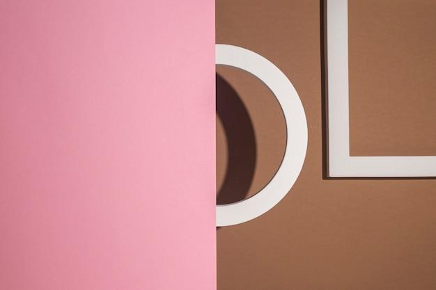 Podio redondo se ve fuera de podiumkvadratny cartón rosa sobre un fondo marrón