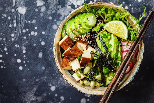 Poke bowl con aguacate, arroz negro, tofu ahumado, verduras, brotes