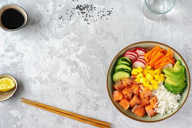 Poke bowl de salmón con aguacate, arroz, zanahorias en vinagre y pepino