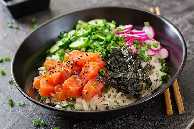 Poke bowl de salmón hawaiano con arroz, rábano, pepino, tomate, semillas de sésamo y algas. tazón de buda. comida dietetica