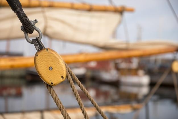 Polea para velas y cuerdas de madera en un viejo barco de vela, con velas y otros barcos fuera de foco