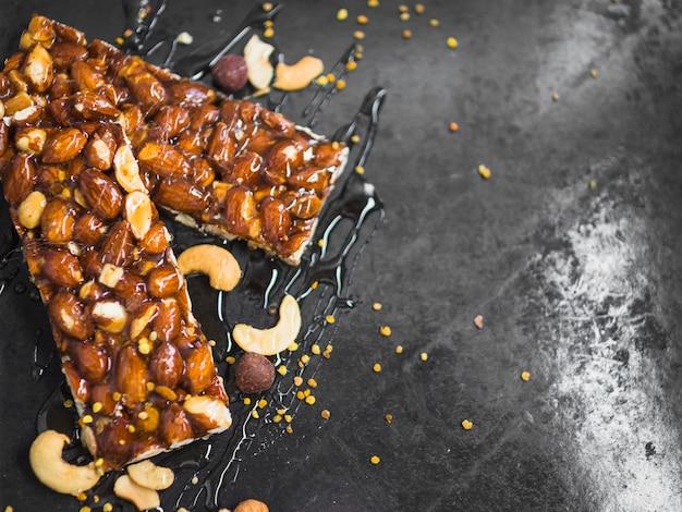 Pólenes de abeja y barras de granola de frutas secas sobre fondo de textura de mármol negro