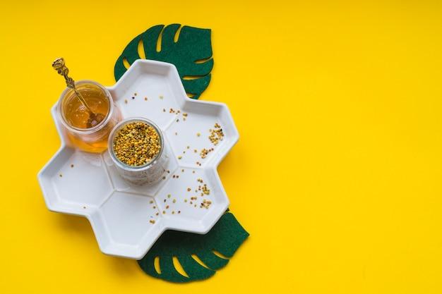 Pólenes de abeja y miel en bandeja blanca sobre fondo amarillo