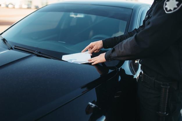 Policía masculino en uniforme escribe una multa en la carretera