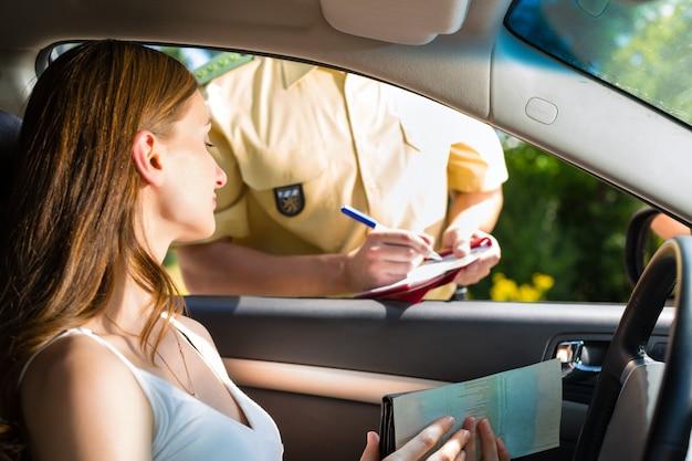 Policía, mujer en infracción de tráfico recibiendo boleto