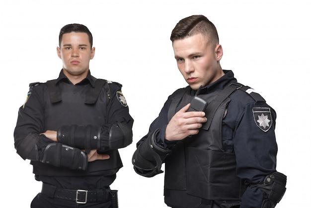 Policías en uniforme y chalecos antibalas en blanco aislado