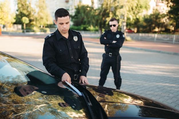 Policías en uniforme escribe auto multa