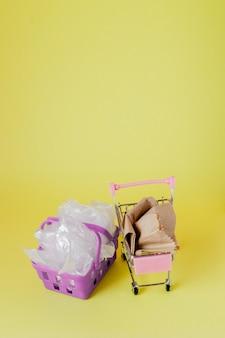 Polietileno y bolsas de papel en una cesta de la compra sobre un fondo amarillo.