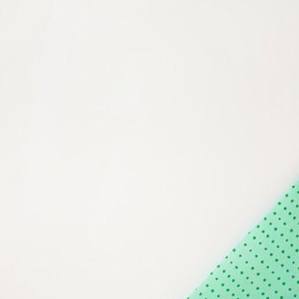 Polka dot verde envuelto en papel en la esquina de fondo blanco