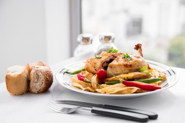 Pollo aderezado con verduras al lado del pan.