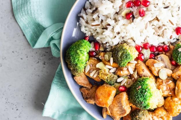 Pollo al curry con arroz, champiñones y brócoli decorado con semillas de granada