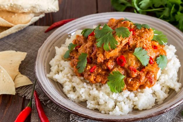 Pollo al curry con arroz y cilantro.