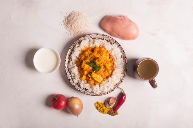 Pollo al curry con arroz e ingredientes en la pizarra