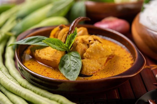 Pollo al curry rojo en un bol con chiles secos, albahaca, pepino y frijoles largos