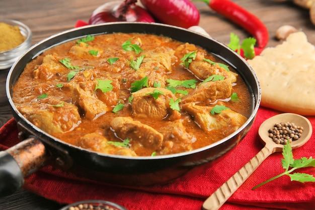 Pollo al curry sabroso en sartén y especias en madera
