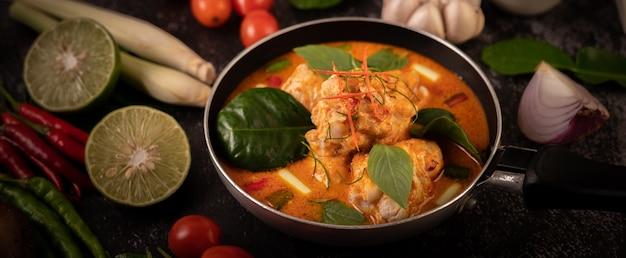 Pollo al curry en una sartén con limoncillo, hojas de lima kaffir, tomates, limón y ajo